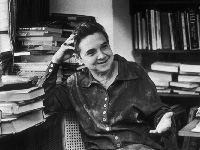 Adrienne Rich seated in front of a desk heaped with books, smiling.
